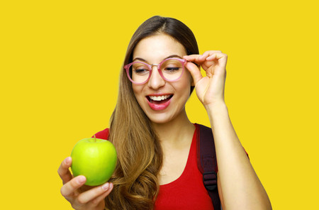 Happy student girl looking her green apple on yellow background 写真素材