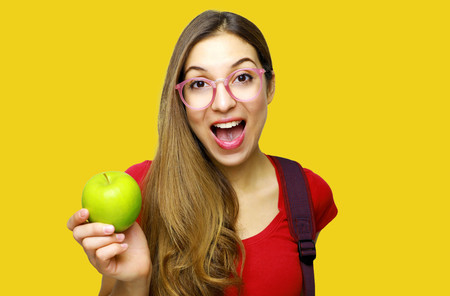 Beautiful young woman over yellow background showing  green apple very happy and excited, winner expression celebrating victory screaming with big smile