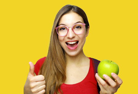 Eat fruits every day. Close up isolated studio portrait of young cheerful girl with long hair in red t-shirt smiling, showing thumb up, holding apple with happy and excited expression. 写真素材
