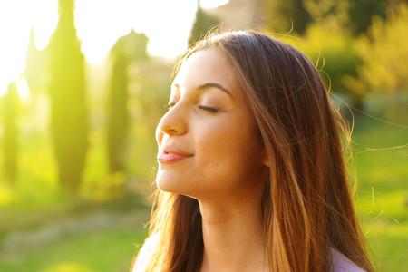 Retrato de perfil de mujer respirando aire fresco profundo con la naturaleza en segundo plano.