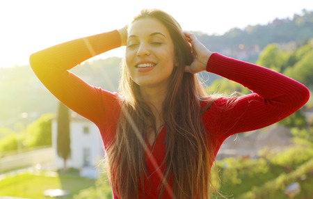 Young woman with raised arms enjoying spring breeze in the park. The sun is shining.