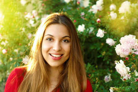 Portrait of young beautiful woman posing among blooming roses in spring time Foto de archivo - 124934842