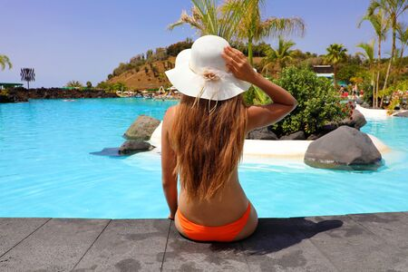 Sexy woman in bikini enjoy tropical resort in Tenerife. Back view girl sitting front pool with hat relaxed. 写真素材 - 124934855