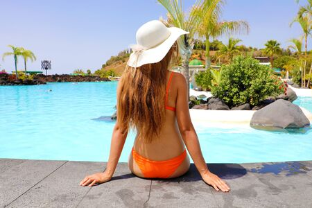 Sexy woman in bikini enjoy tropical resort in Tenerife. Back view girl sitting front pool with hat relaxed.
