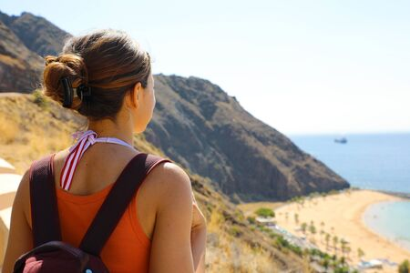 Back view from terrace of traveler girl looks to Playa de Las Teresitas seascape, Tenerife, Canary Islands