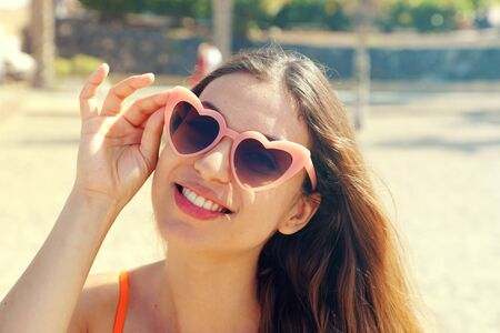 Pretty brunette woman in pink heart lolita sunglasses on the beach. Holidays, vacation travel and freedom concept. Beautiful happy girl in heart shaped sunglasses on beach.