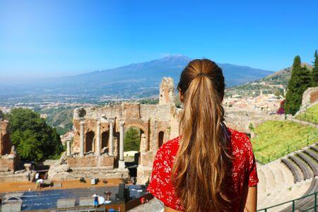 Schönes junges weibliches Modell in den Ruinen des antiken griechischen Theaters in Taormina mit dem Vulkan Ätna im Hintergrund, Sizilien Italien