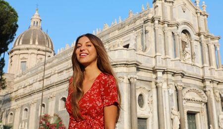 Viaggio in Sicilia. Bella ragazza sorridente in visita al Duomo di Catania al tramonto. Vacanze estive in Italia. Archivio Fotografico
