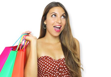 Excited fashion woman holdings shopping bags and looks up the copy space on pink background.