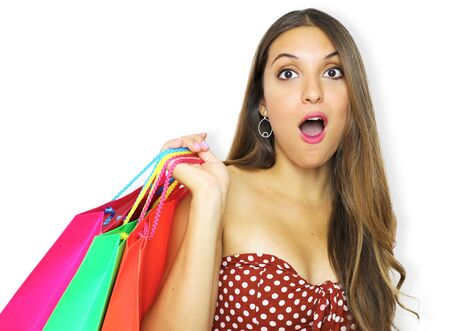 Portrait of a pretty shocked fashion girl holding shopping bags isolated over pink background.