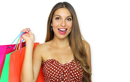 Portrait of young happy smiling woman with shopping bags isolated over white background with copy space.