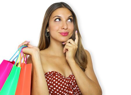 Fashion woman holding shopping bags and looking up to the side on white background at copy space. Elegant young beautiful brazilian woman thinking and looking up happy.