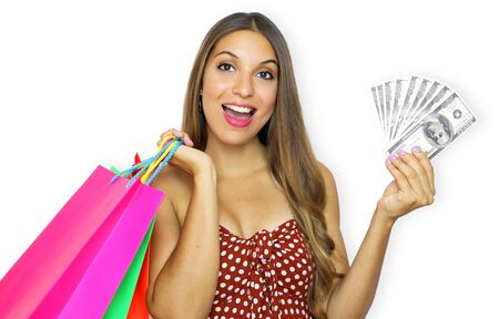 Happy portrait of young smiling fashion woman looking at camera with shopping bags and bunch of money in her hands.