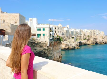 Back view of beautiful young woman in Polignano a mare town on Mediterranean Sea, Italy.