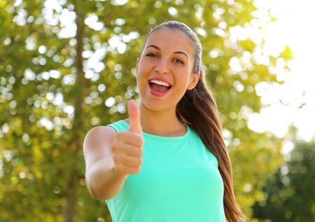 Super woman! Portrait of winner girl showing thumb up. Positive smiling fitness healthy woman outdoor. 写真素材