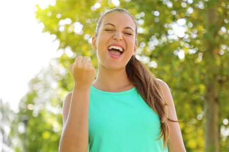 Success winner fitness runner woman screams of satisfaction with closed eyes and fist up energetic powerful anger force determination strength expression celebrating.