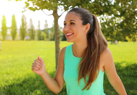 Smiling sporty woman running outdoors in park.