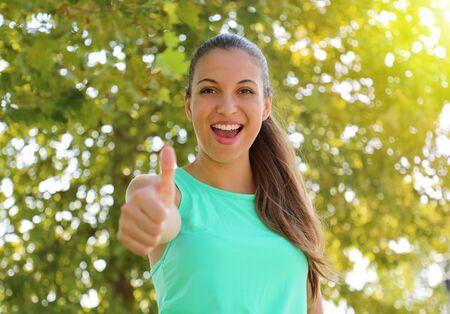 Acuerdo de mujer hermosa fitness con el pulgar hacia arriba al aire libre con un fondo verde desenfocado.