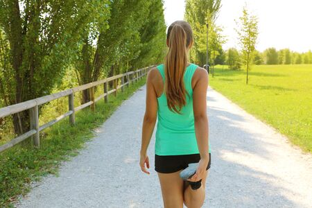 Young fitness woman runner stretching legs before run in the park. 写真素材