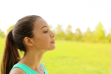Side view portrait of woman relaxing breathing fresh air deeply in the park. Copy space.