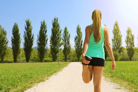 Young runner woman doing stretching in the park before run. Copy space.