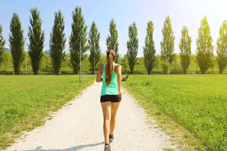 Young sporty woman running in park. Fitness girl jogging in park. Rear view of sporty girl running on pathway.
