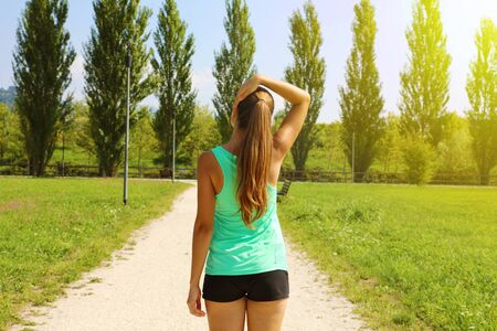 Back view of young runner woman stretching neck in the park.