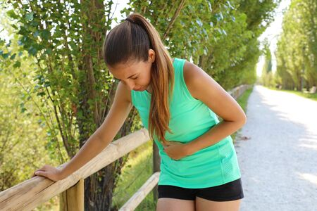 Woman has side cramp. Young woman suffering from abdominal pain while running outdoor.