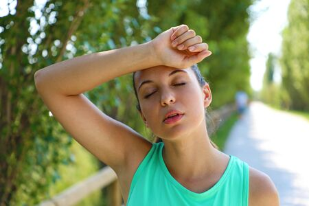 Close up of young woman taking a break from working out outside tired with arm over head. Stok Fotoğraf