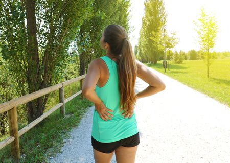 Back pain. Athletic running woman with back injury in sportswear rubbing touching lower back muscles standing outside in the park.