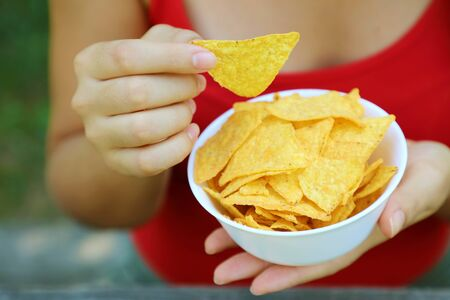 Hand take tortilla chip from a full bowl.