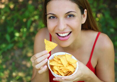 Beautiful young woman eating tortilla chips outdoor.