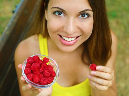 Close up of beautiful sexy woman eating raspberries in the park.