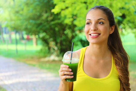 Fitness woman holding green detox smoothie and looking to the side with copy space. 写真素材