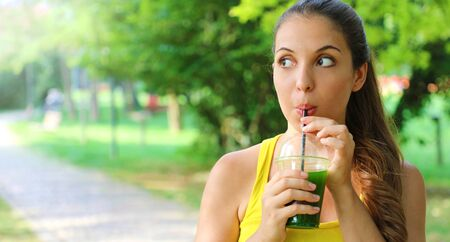 Young beautiful woman drinking green detox smoothie. Fitness girl drinking vegetable smoothie after fitness running workout. Panoramic banner view with copy space.