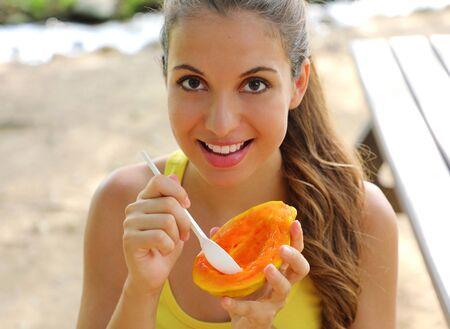 Beautiful brazilian woman eating papaya fruit outdoor. 写真素材