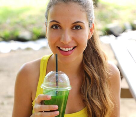 Close up of fitness girl looking at camera and holding green detox juice outdoor.