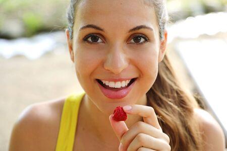 Close up of beautiful girl eating berries outdoor. 写真素材