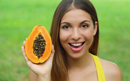 Beautiful brazilian woman holding papaya fruit in her hand with green backgroud. 写真素材