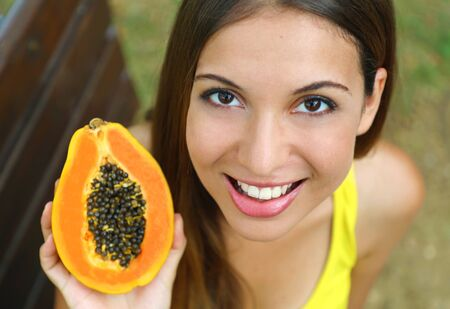 Close up of young woman showing papaya healthy fruit outdoor.