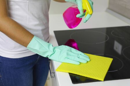 Woman hands cleaning a modern black induction hob by a rag and spray. Banque d'images - 129596952