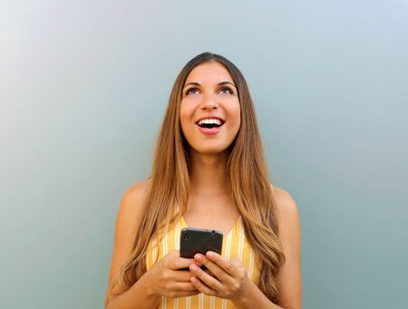 Surprised beautiful girl looking up the copy space while texting on smart phone.