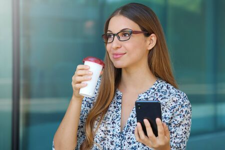 Portrait of a smiling business woman using mobile phone while holding cup of coffee before to go at work and looking away.