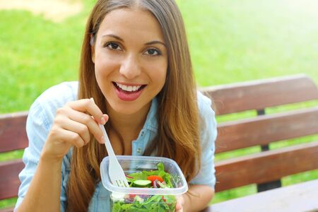 Happy smiling woman eating salad sitting in the park looks at camera with copy space area. Lunch salad take out container healthy eating young business woman ready to eat in park living lifestyle. Stock fotó