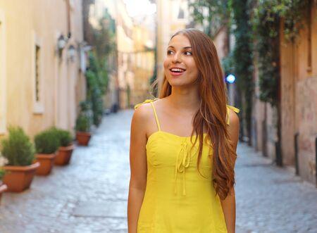 Ritratto di bella donna alla moda con i capelli lunghi in abito estivo giallo che cammina ed esplora il quartiere di Trastevere a Roma, Italia.