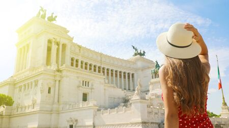 Travel in Rome. Back view of beautiful girl visiting Altar of the Fatherland famous landmark of Rome. Summer holidays in Italy. Stock Photo