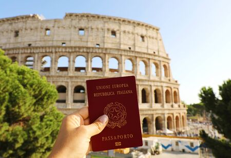 Citizenship concept: hand hold Italian passport in front of Colosseum in Rome. Stock Photo