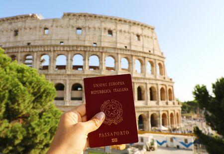 Concepto de ciudadanía: sujete el pasaporte italiano frente al Coliseo de Roma.