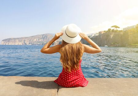 Beautiful young woman with hat sitting on the edge looking at stunning panoramic village of Sorrento on Sorrentine Peninsula, Italy.