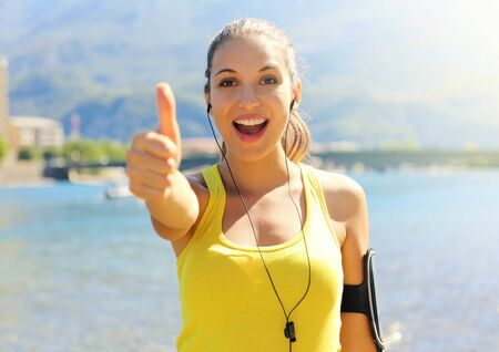 Super woman! Portrait of winner girl showing thumb up. Positive smiling fitness woman outdoor. Happy beautiful fitness woman active wear and sports arm band for phone and earphones workout on beach. Reklamní fotografie